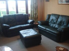 two bottle green leather sofas and footstool