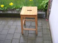 A four legged wooden stool with hand slot in seat.