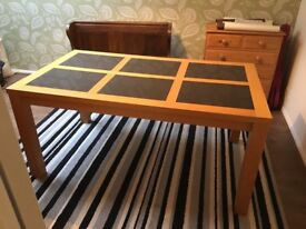 Large wooden dining room table with smokey glass inserts.