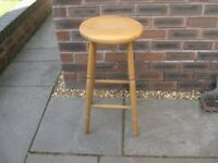 A tall pine stool with a larger than usual concave seat.