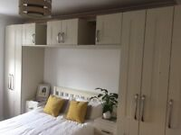 Bedroom wardrobes with bridging unit above the bed