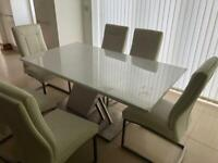 Glass dining table with 8 white leather back chairs in excellent condition very comfortable