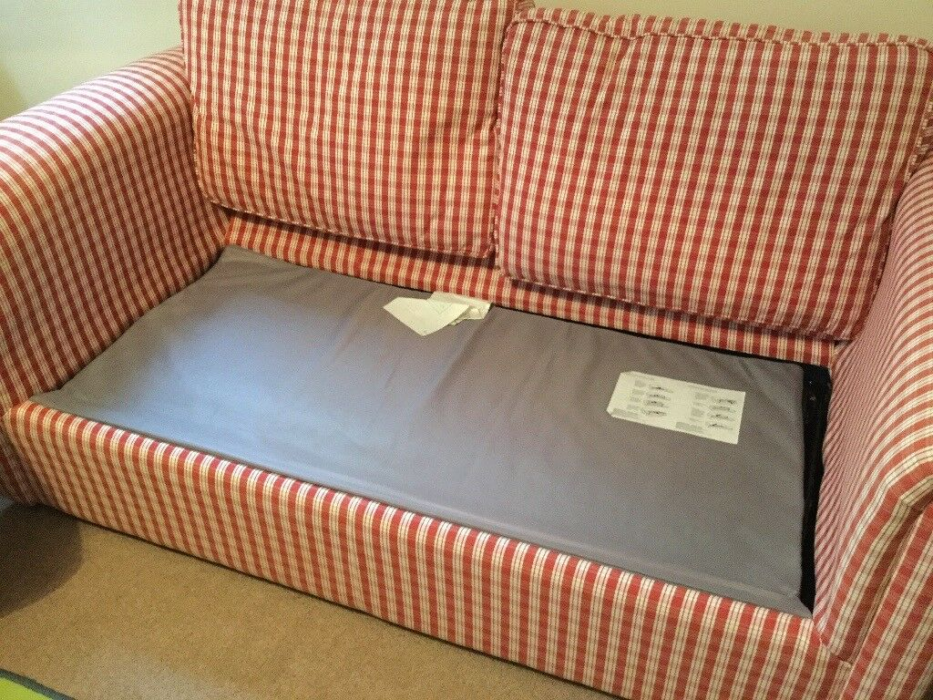 Metal frame fold out sofa bed in red and cream check.