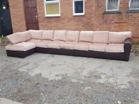 Lovely BRAND NEW very very large corner sofa. Brown leather base.fabric cushions.can deliver