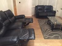 Black genuine leather 3 & 2 seater reclining sofas.