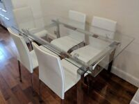 A glass top dining table with 6 chairs