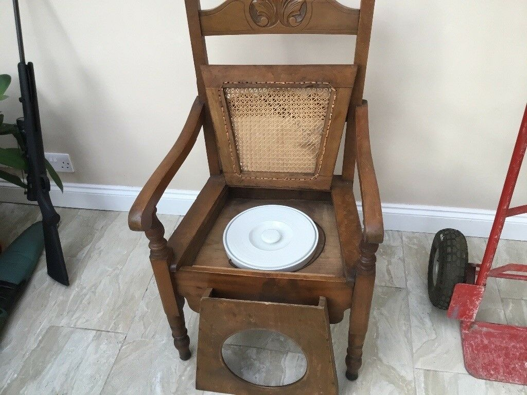 A very old wooden commode chair complete with original potty and lid ...