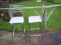 Two dining/kitchen stools. Colour: grey seat cover, stainless steel. Height from bottom to top 100cm
