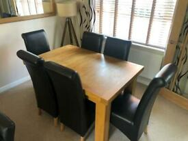 Extendable light oak dining table and chairs