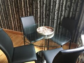 Glass table and four black chairs