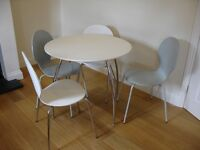 Round white dining table with chrome legs and four chairs