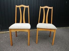 Two solid wooden dining chairs.