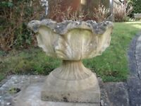 A PAIR OF STONE URN SHAPED GARDEN PLANTERS