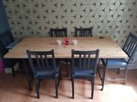 Dining table and 6 Chairs- solid wood top and metal frame. Black chairs with grey cushions.