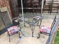 Garden glass table and 4 chairs, massively solid iron frame.