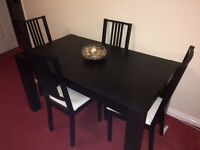 Black wood dining table and four chairs