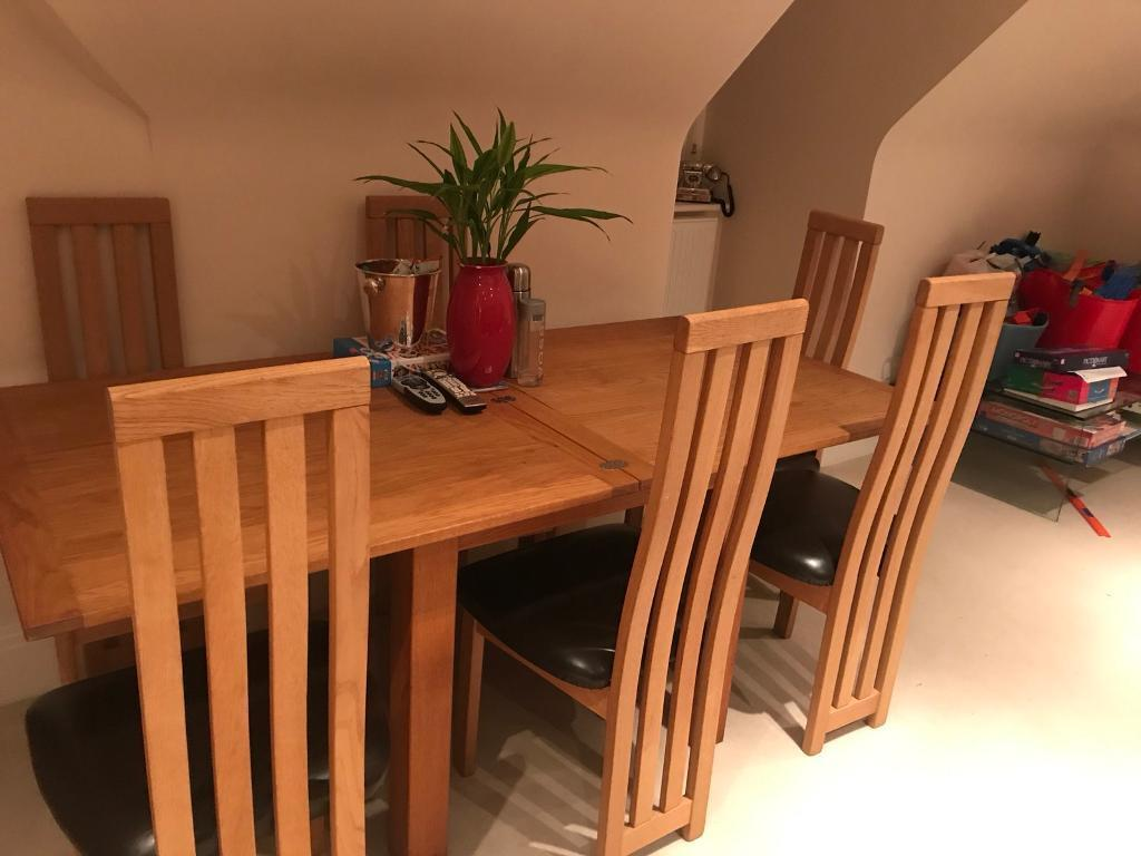 Oak table- extendable with six chairs in brown leather