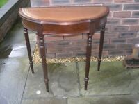 An attractive half moon hall table with leather top.