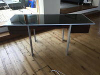 Steel and wood office desk with glass (black) table top. Four drawers and keyboard pull out shelf.