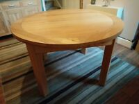 Extending round solid oak dining table