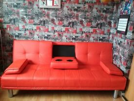 Red faux leather sofa bed with cup holders