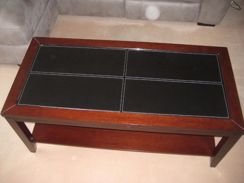Dark wood coffee table with glass top and black leather insert wooden lower shelf