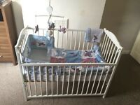 White wooden cot with 5 piece bedding including musical mobile