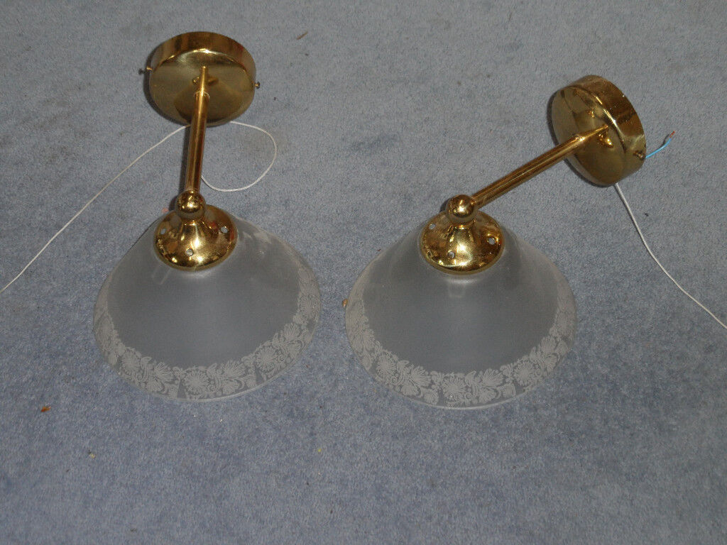 Two wall lights in polished brass with frosted glass shades, individually switched