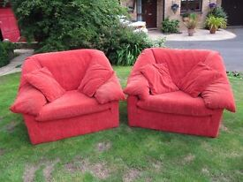 2 large red fabric armchairs with 4 matching scatter cushions