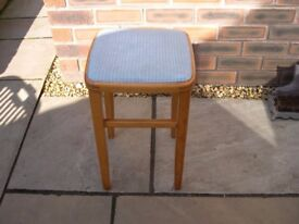 A wooden four legged stool with blue vinyl top.