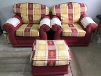 two red and yellow one seater sofa chairs with a pouffe foot stool
