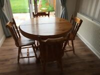 Round extending pine dining table and six chairs
