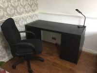 Ikea black desk with large swivel chair.