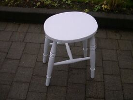 A white wooden stool with oval seat.