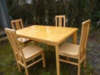 Light wood extending dining table and four high-backed chairs with rattan seats