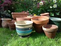 Assorted rustic terracotta and glazed pots with decorative pump