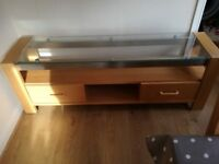 Oak TV unit with glass top and two drawers.