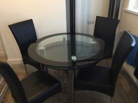Solid Glass Table With four Black Leather Chairs
