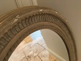 Pretty oval mirror with carved wooden frame in a distressed grey paint finish
