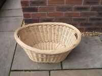 A wicker laundry basket with integral handles.