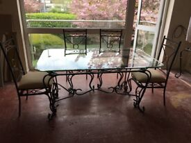 Glass topped metal framed dining table with 6 matching chairs.