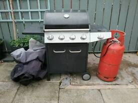 Gas barbeque with side burner and gas bottle.