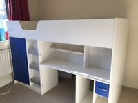High sleeper children's bed with integrated wardrobe, drawers, shelves and desk.