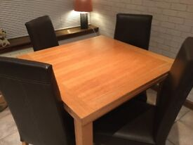 Oak extending dining table and 6 brown faux leather chairs