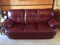 Two matching burgundy real leather sofas