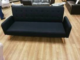 Black fabric sofabed witb arms and wooden legs folds down to bed