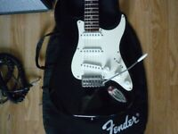 Fender Squier stratocaster, an amplifier, lead and cordless microphone.