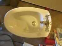 Beige bidet with brass fittings
