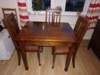dark wood dinning table and four chairs with pink leather cushions