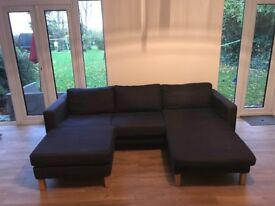 Sofa. This four seater sofa with separate foot stool has grey and beige covers.